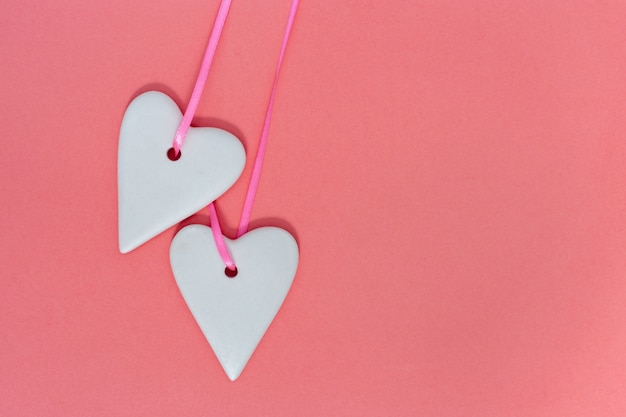 Two ceramic hearts earts white colored close up on paper pink