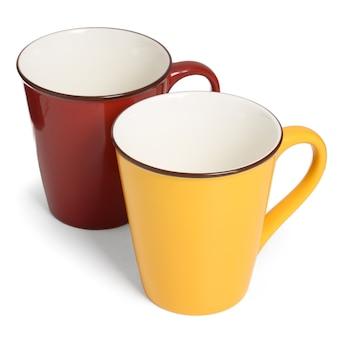 Two ceramic mugs on white, empty red and yellow mug