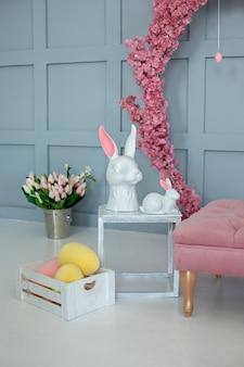 Две керамические статуэтки пасхальных кроликов стоят на деревянном столе пасха интерьер комнаты