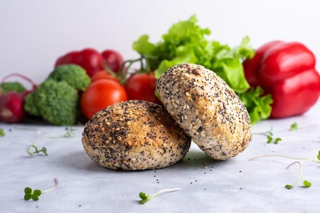 赤と緑の野菜と白いプレート上の2つのシリアルパン。