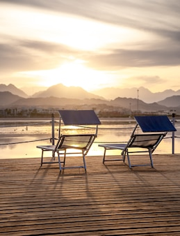 Two chairs on the pier overlooking the sunset among the mountains. a place of rest and relaxation.