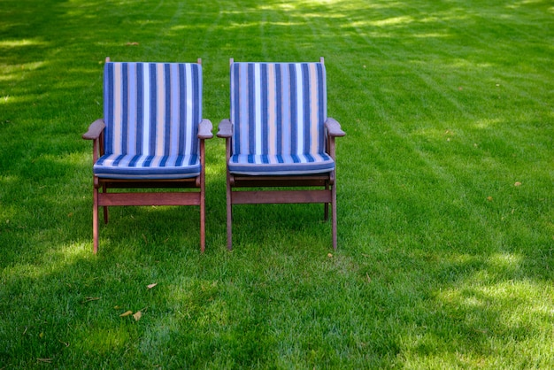 Two chairs with striped mattresses on a green grass