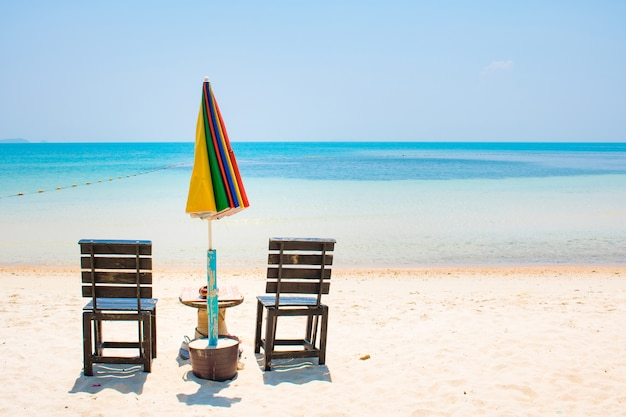 Two chairs with umbrela on white sand beach and blue sea in samed island, thailand