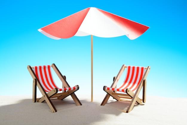 모래 해변에서 우산 아래 두 긴의 자