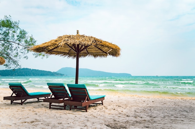 Two chaise longues under a straw umbrella on a beach near the sea. tropical background. coast of island koh rong samloem, cambodia.