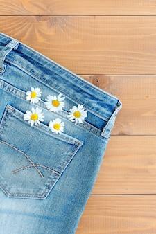 ジーンズのポケットに2つのカモミールの花。ブルージーンズの背景にデイジー。夏のグリーティングカード