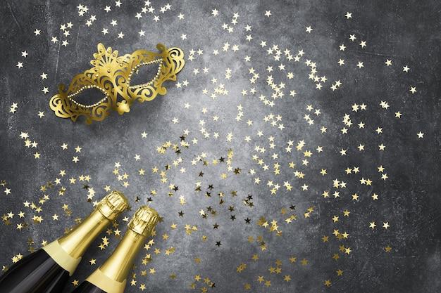 두 샴페인 병, 황금 카니발 마스크 및 회색 배경에 색종이 별. 크리스마스