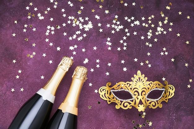 Две бутылки шампанского, золотая карнавальная маска и звезды конфетти на фиолетовом. плоская планировка