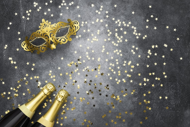 Two champagne bottles, golden carnival mask and confetti stars on grey background. christmas
