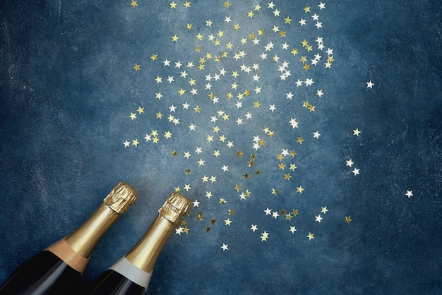 Two champagne bottles with golden confetti on blue background.
