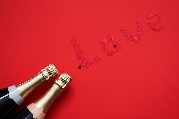Two champagne bottles with hearts shaped confetti forming word love on red background.