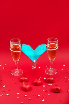 Two champagne glases, candy and medical mask valentine on red.
