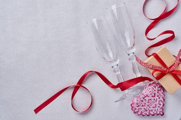 Два бокала для шампанского, подарочная коробка, красивая саржа и красная лента на сверкающем сером фоне. валентинка. вид сверху.