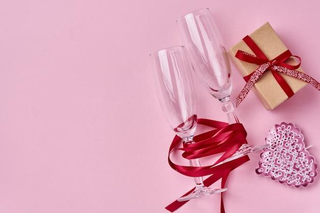 Два бокала шампанского, подарочная коробка, красивая саржа и красная лента на сверкающем розовом фоне