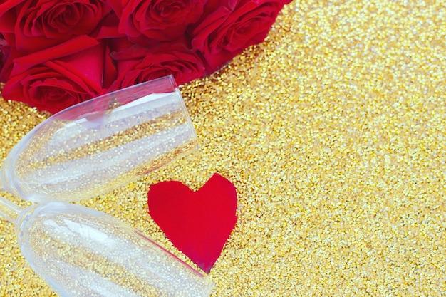 Два бокала для шампанского, красный букет роз и сердце из лепестков лежит сбоку на ярком золотом ...