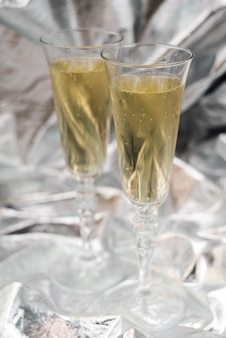 Two champagne glasses on blurred silver background