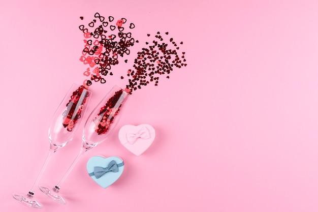 Два бокала для шампанского, наполненные блестками в форме сердца, с бутылкой шампанского и подарком ко дню святого валентина на розовом фоне.