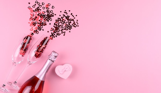 Two champagne glasses filled with heart shaped sequins with a bottle of champagne and a valentine's day gift on a pink background.