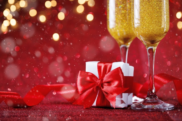 Two champagne glasses and gift box on red glitter background