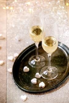 Два бокала для шампанского на подносе, стоящем на серебряном сверкающем столе, белые сердца, огни боке. сервировка праздничного стола.