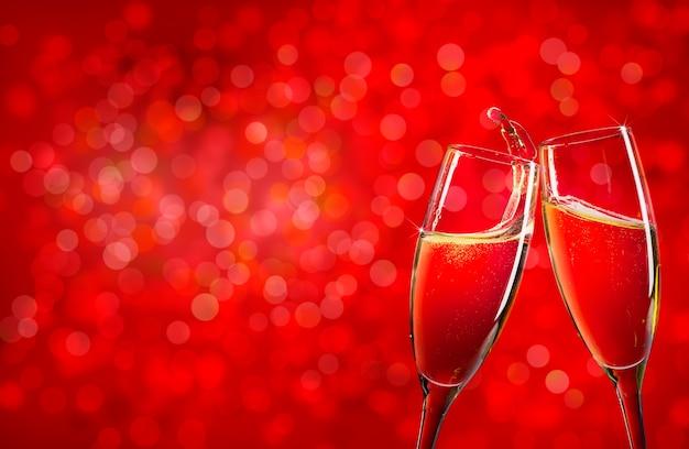 コピースペースと赤いクリスマスの背景の上の2つのシャンパングラス