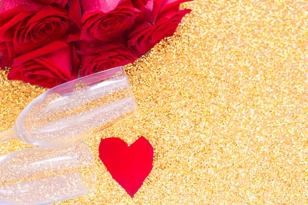 Two champagne glasses a red bouquet of roses and a heart of petals lies on the side on a bright gold...
