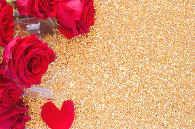 Two champagne glasses and a red bouquet of roses lies on the side on a bright gold background with a...
