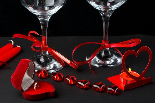 Два бокала для шампанского, перевязанные лентами на черном фоне, рядом с коробкой в форме сердца с кольцом и подсвечником. горизонтальное фото