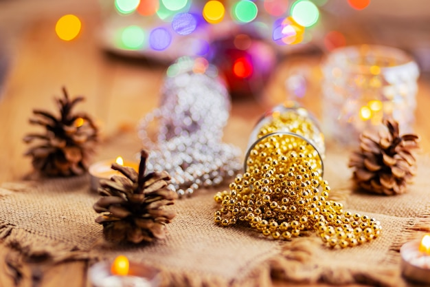 Two champagne glasses with christmas beads. christmas decorations in rustic style on bright background with lights. pine cones and burning candles on the background bokeh