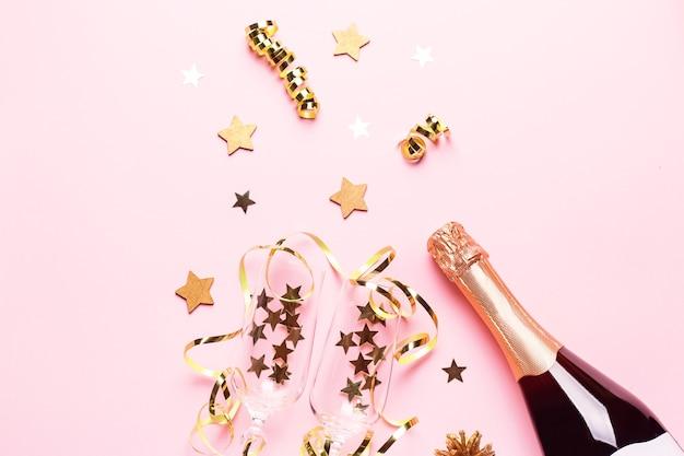Два бокала для шампанского с конфетти и растяжками, золотая бутылка шампанского, зеленая натуральная ель на пастельно-розовом фоне, копия пространства. праздничная плоская композиция на рождество или новый год