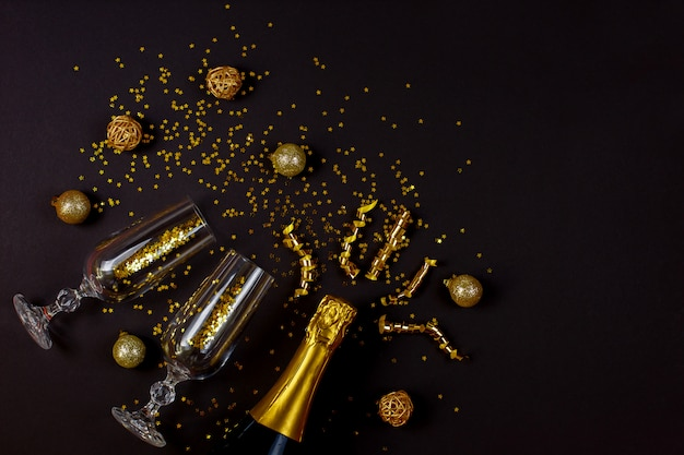 Two champagne glasses with confetti on black background.