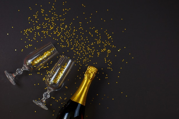 Two champagne glasses with confetti lying on black background. new year celebration concept. top view. festive flat lay.