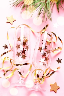 Two champagne glasses with confetti and streamers in pink and gold colors