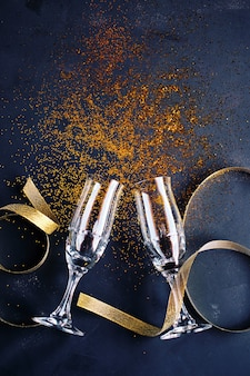 Two champagne glasses with glitter on a black background symbolizing a celebration