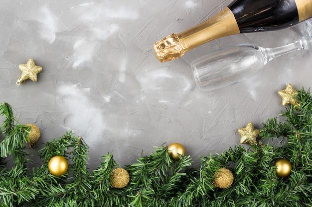 ゴールドボールとゴールデンシャンパンボトル、灰色のテーブル、コピー領域の緑のモミの木の2つのシャンパングラス。クリスマスのお祝いフラットレイアウト構成