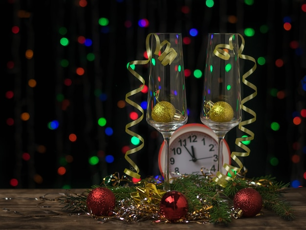 Two champagne glasses with ornaments and a clock on a bokeh