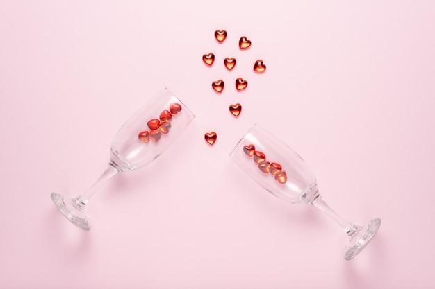 Два бокала для шампанского с сердечками из красного стекла над розовой поверхностью.