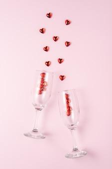 Два бокала для шампанского с сердечками из красного стекла над розовым.