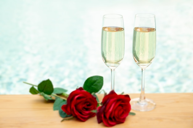 Two champagne glasses with rose flower next swimming pool.