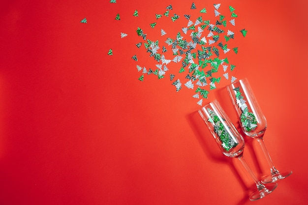 Two champagne glasses with splashing confetti in the form of christmas trees on a red background. new year and christmas concept. copy space