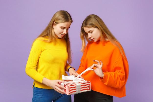생생한 옷에 두 매력적인 금발 쌍둥이 자매 소녀 보라색 파란색 벽에 고립 된 선물 리본이 달린 빨간색 줄무늬 선물 상자를 개최. 사람들이 가족 생일, 휴가 개념.