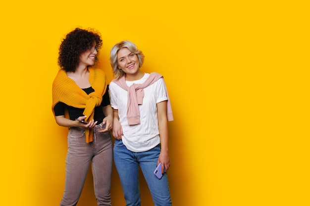 Two charming curly haired sisters are posing on a yellow  wall smiling at front near free space