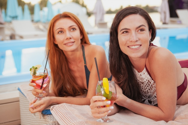 Two charming female friends relaxing by the swimming pool