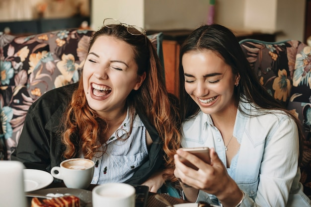 Two charming girlfriend sitting in a cafe and laughing with closed eyes while holding a smartphone.