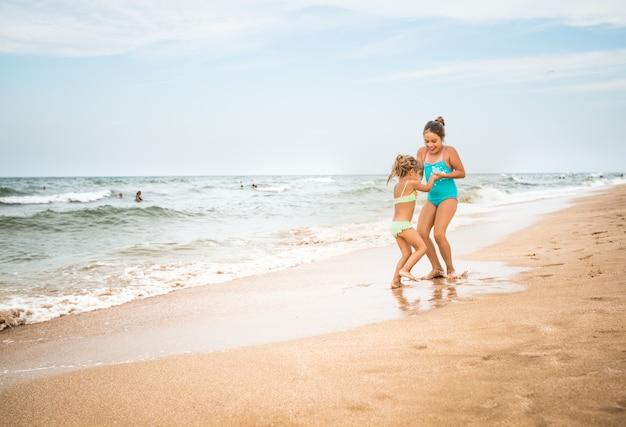 Две очаровательные маленькие девочки в купальниках танцуют на песчаном пляже у моря на фоне голубого неба в теплый летний день