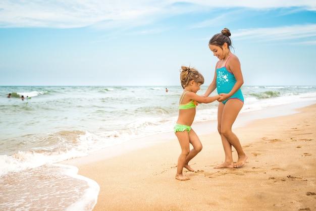 수영복에 두 매력적인 어린 소녀가 따뜻한 여름날에 푸른 하늘을 배경으로 바다 근처의 모래 사장에서 춤을 추고 있습니다.