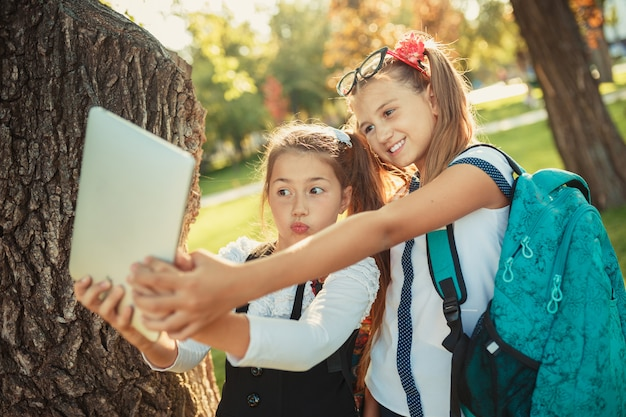 Two charming school-age girls are standing by the tree next to the school and playing on the tablet. schoolgirls take a selfie