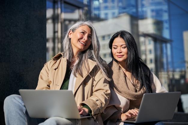 路上でラップトップを使用している2人の魅力的な女性