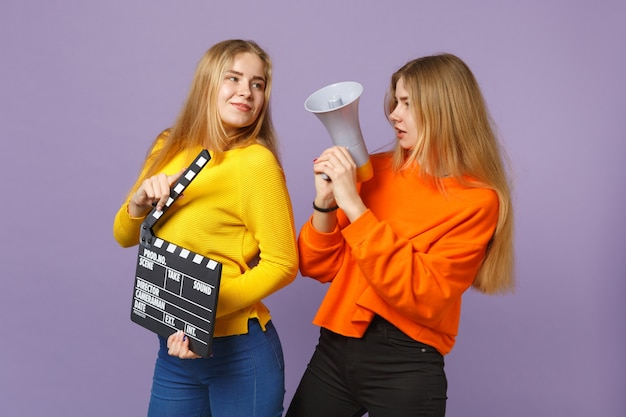 Две очаровательные молодые блондинки сестры-близнецы держат классический черный фильм, снимая с хлопушкой, крича в мегафон, изолированного на фиолетово-синей стене. концепция семейного образа жизни людей. .