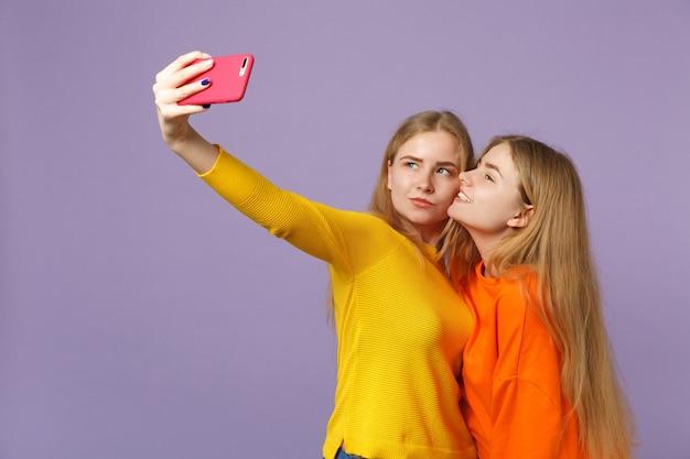 パステルバイオレットブルーの壁に隔離された携帯電話でselfieショットをしているカラフルな服を着た2人の魅力的な若いブロンドの双子の姉妹の女の子。人々の家族のライフスタイルの概念。